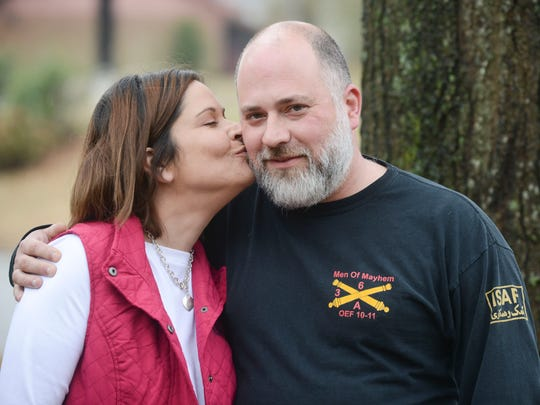 Hollie and John Lowe share a kiss in front of their home in Milan on Tuesday afternoon. Lowe had a hard time finding work after he returned from overseas, where he served in the U.S. Army, but has finally found work at a factory.
