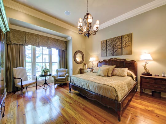 The master bedroom features wood floors and views of the garden.
