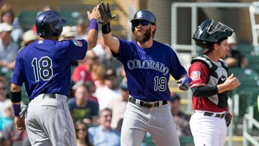 Rockies' Cristhian Adames (18) and Charlie Blackmon (19) high five after the pair scored in the third inning of the Spring Training game against the Diamondbacks at Salt River Fields at Talking Stick on Thursday, March 3, 2016.