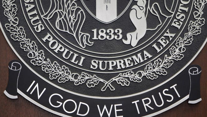 "The Greene County seal in the commissioners chambers in the Historic Courthouse includes the motto ""In God We Trust."" A move to have the same posted in Springfield City Council chambers had died."