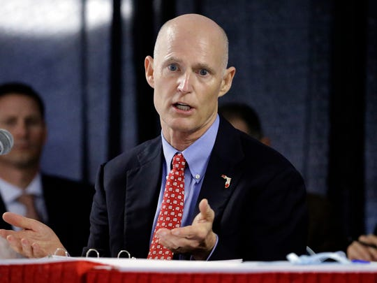 In this Feb. 5, 2015, file photo, Florida Gov. Rick Scott gestures during a cabinet meeting at the Florida State Fair, in Tampa, Fla.