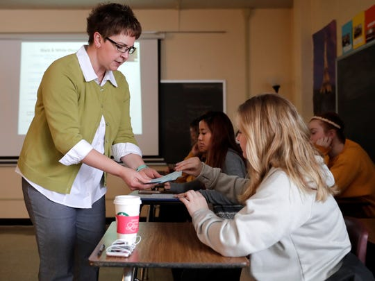 Barbara Jirikowic hands out notecards to Callee Engelmann, a senior, during the Race, Rights and Transcultural Beliefs class at Neenah High School.