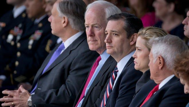 U.S. Sen. John Cornyn sits with U.S. Sen. Ted Cruz and wife Heidi Cruz at a Fort Hood Purple Heart ceremony on April 10, 2015.