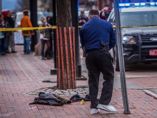 Burlington police investigators examine the scene of