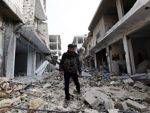 A member of Syrian Kurdish People's Defense Units walks
