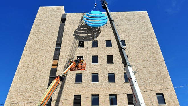 Workers from Willow Creek Signs hang a new AT&T sign Wednesday afternoon on the downtown AT&T building. Workers said when finished, the sign will light up at night with an almost white glow.