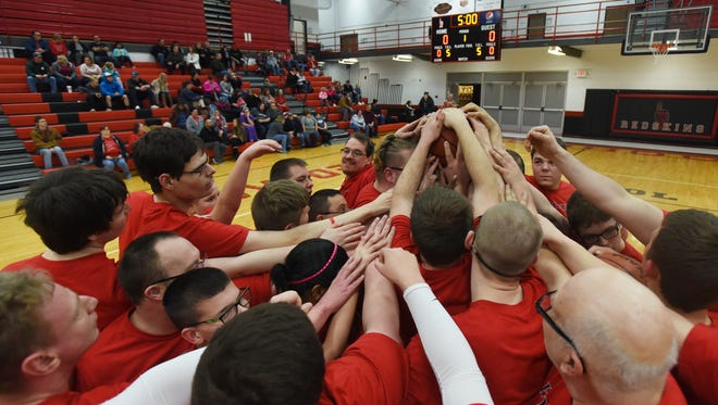 The Indians gather at center court before taking on the staff of the Coshocton County Board of Developmental Disabilities during the two team's annual basketball game at Coshocton High School on Wednesday.