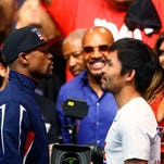 Floyd Mayweather (left) stares at Manny Pacquiao during weigh-ins for Saturday's boxing match at MGM Grand.