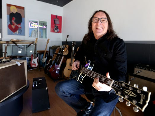 Owner Tim Knight plays a guitar inside the newly opened