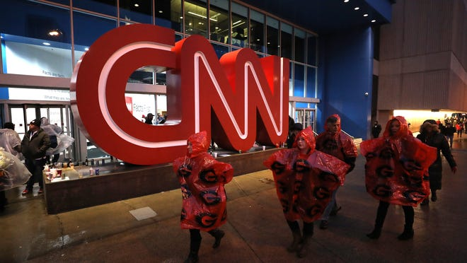 ATLANTA, GA - JANUARY 08: Fans walk past the CNN Center en route to the CFP National Championship presented by AT&T between the Georgia Bulldogs and the Alabama Crimson Tide at Mercedes-Benz Stadium on January 8, 2018 in Atlanta, Georgia.  (Photo by Christian Petersen/Getty Images)