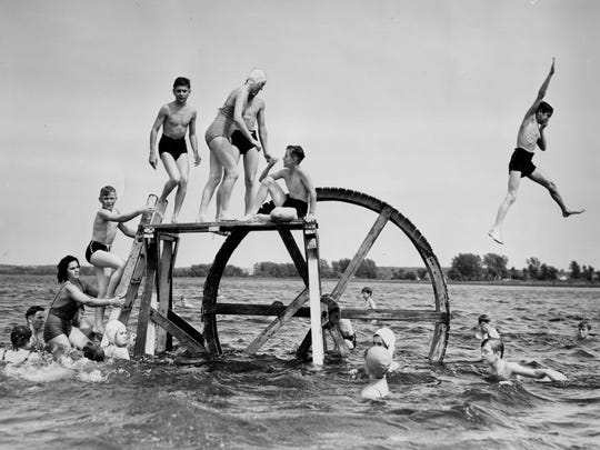 Beach goers in this historic photo enjoy themselves at Bay Beach, where fun-seekers could rent a bathing suit and splash in the water.