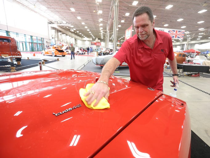 The 55th annual World of Wheels at the Indiana State Fairgrounds runs from Friday February 7th-9th. Here Frank Tuton rubs a the 1970 'Cuda he restored for a client.