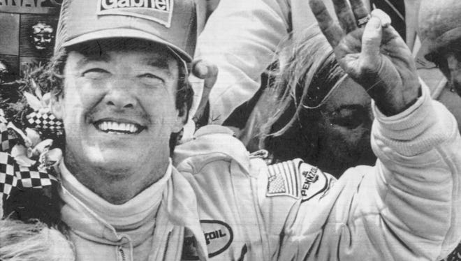 Johnny Rutherford holds up three fingers to indicate his third Indy 500 win. May 25, 1980.