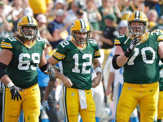 Green Bay Packers quarterback Aaron Rodgers (12) is flanked by his offensive linemen tackle David Bakhtiari (69) and guard T.J. Lang (70) against the Detroit Lions at Lambeau Field.