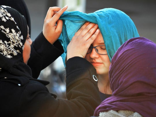 """A Muslim student, left, helps Sarah Pooley, 14, of Albuquerque, try on the traditional head covering known as a hijab on the campus of the University of New Mexico in Albuquerque Wednesday, Feb. 1, 2017. Students took part in """"World Hijab Day"""" on Wednesday, an event created in 2013 in reaction to Muslim women being harassed for wearing the head covering used by some women who practice Islam."""
