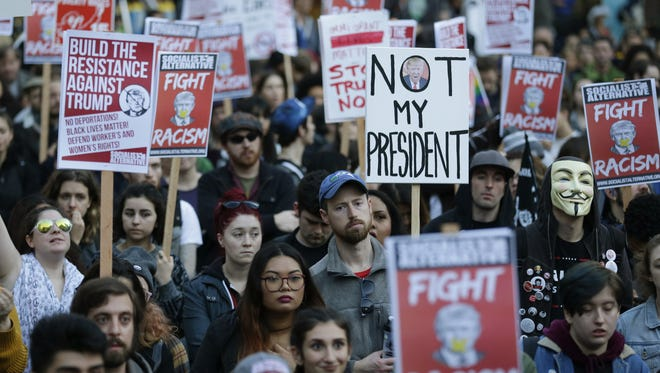 People hold signs as they listen to speakers at a protest against the election of President-elect Donald Trump, Wednesday, Nov. 9, 2016, in downtown Seattle.