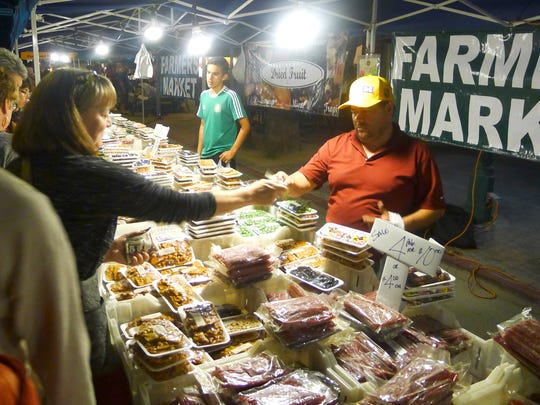 Armando Avelar (right) has sold produce at VillageFest for nearly 25 years.