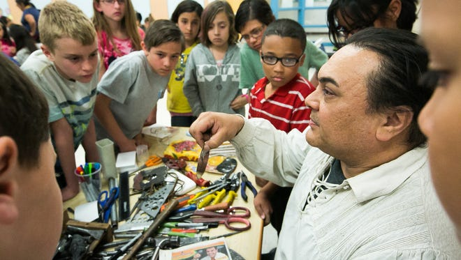 Jason Younis y Delgado, a fifth generation tin smith, of Albuquerque, New Mexico, teaches an art class at Fairacres Elementary School on Thursday. Younis y Delgado is in town for the Las Cruces Spanish Market that will be held at Hotel Encanto on Saturday at Sunday.