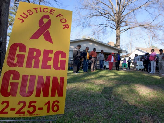 Members of the community hold a vigil, on Saturday February 25, 2017, for Greg Gunn one year after he was shot and killed, by Montgomery police officer Aaron Cody Smith, in front of his home on McElvy Street in Montgomery, Ala.