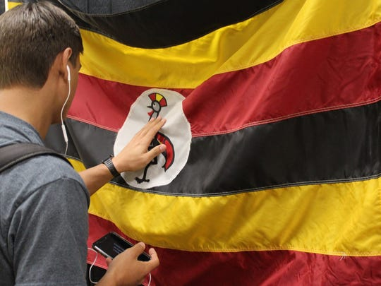 Jonathan Raitz, a senior from Bandera, touches the flag of Uganda while touring an refugee exhibit that's part of Summit this week at Abilene Christian University.