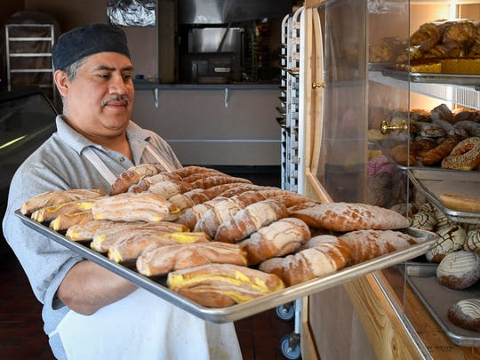 Miguel Ochoa baker, at the Panaderia San Miguel bakery puts a tray of cinnamon bread in to the display case Wednesday, June 6, 2018.
