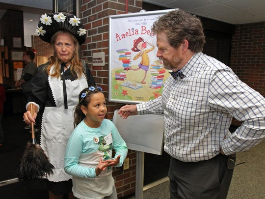 """Herman Parish, author of Amelia Bedelia children's books, greets visitor Meaghan Keegan during his visit to Middlesex County College for Make A Difference Day in Middlesex County. At left is """"Amelia"""" portrayed by Patti Brauer of Edison."""