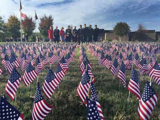 Community leaders and students look at the 6,718 flags