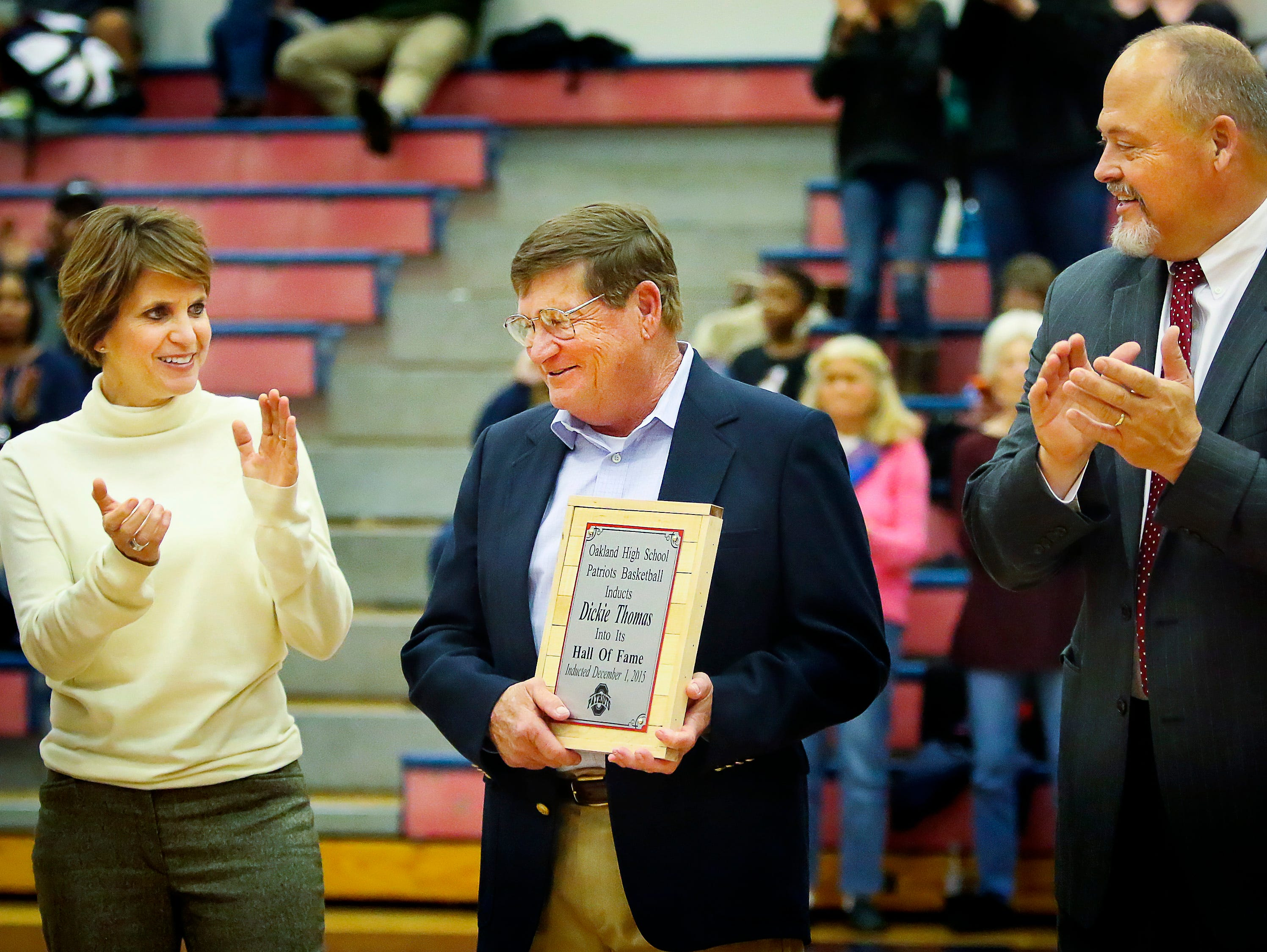 Former Oakland coach Dickie Thomas, center, is honored after being named to the school's basketball hall of fame. To his left is Oakland girls coach Jennifer Grandstaff. Right is Oakland principal Bill Spurlock.