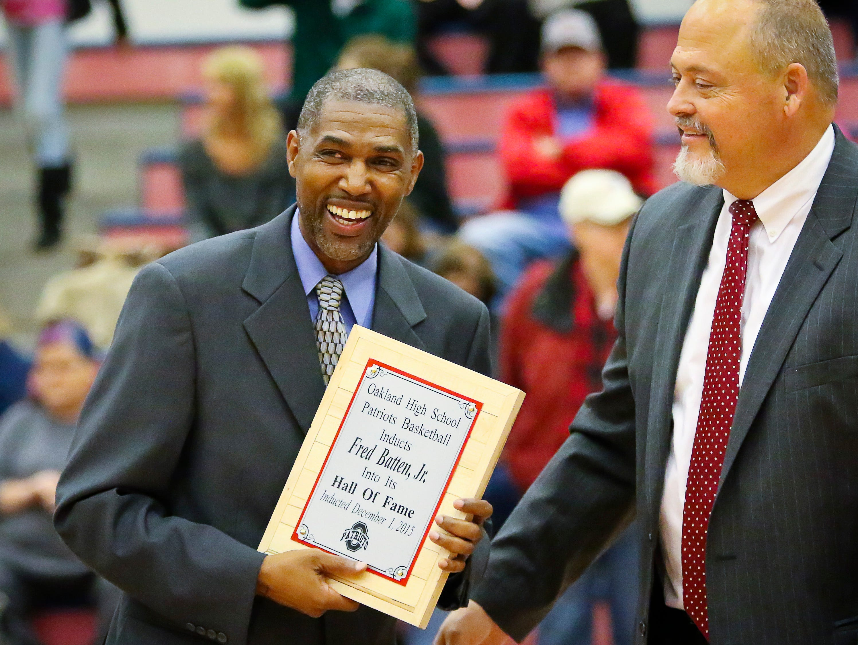 Former Oakland standout Fred Batten Jr. receives a plaque signifying his induction into the Oakland High Basketball Hall of Fame.