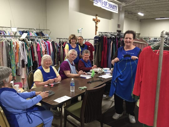 Volunteers get ready for the Ladies of Charity spring sale, which opens Friday at the Ladies of Charity shop.