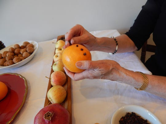 Cloves are inserted into a fresh orange that will embellish