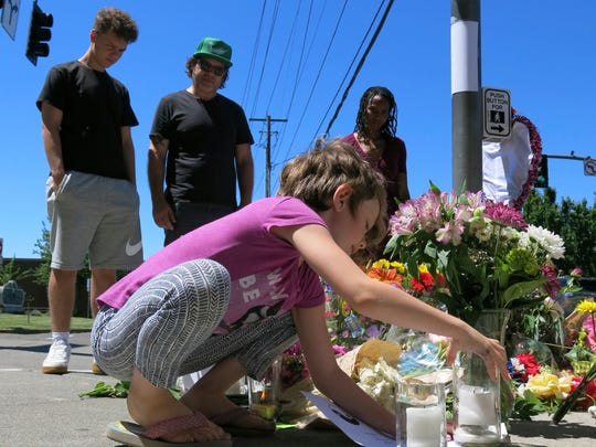Coco Douglas, 8, leaves a handmade sign and rocks she painted at a memorial in Portland.