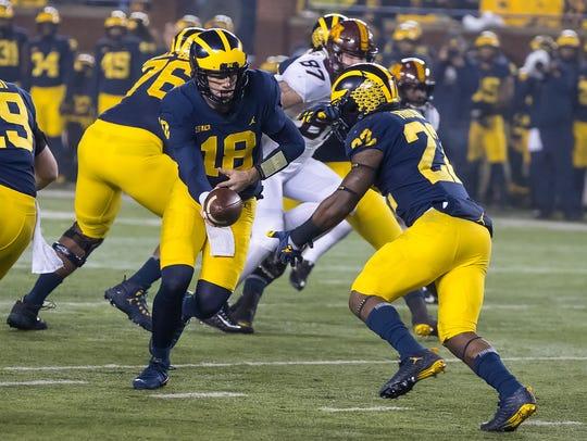 Michigan's Brandon Peters hands off to Karan Higdon