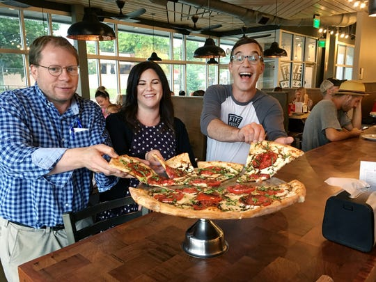The owners of Five Points Pizza show off one of their 20 inch pies. From left, Tanner Jacobs, and Tara and David Tieman.