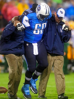 Titans offensive lineman Chris Spencer is helped off the field after suffering an ankle injury against the Packers.