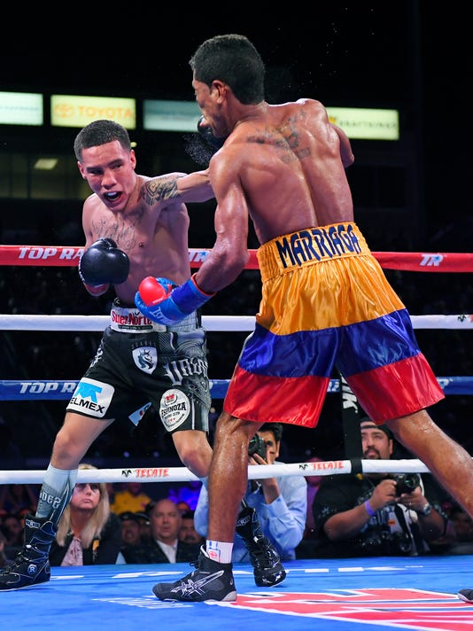 Oscar Valdez, Jr., left, of Mexico, connects with Miguel Marriaga, of Colombia, for a knockdown during the 10th round of a WBO featherweight world championship bout, Saturday, April 22, 2017, in Carson, Calif. (AP Photo/Mark J. Terrill)