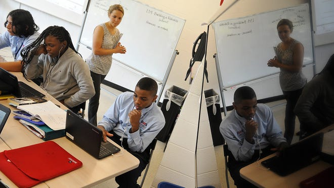 Students Alessandro Ponce, Jasmine Gift and Cameron Moffett watch a video on their laptops at RePublic, a computer science-focused school, as teacher Delaine Wendling looks on.