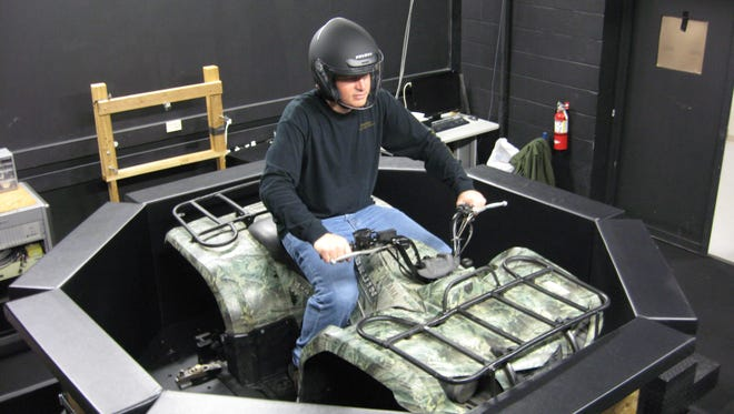 An articulate advocate for ATV safety, Dr. Charles Jennissen is shown testing an ATV driving simulator under development at the Center for Computer-Aided Design on the University of Iowa campus, part of the College of Engineering.