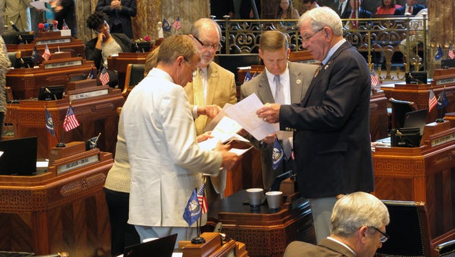 Senators look at a spreadsheet outlining a proposed budget compromise in the final hours of the special legislative session on taxes, on Thursday,.
