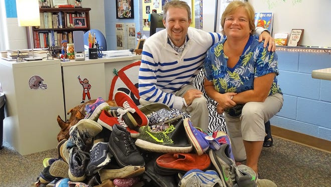 Eighth-grade language arts teacher Mason Roulston and guidance counselor Jayne Clingel show off the 180 pairs of shoes that his first-period class has collected.