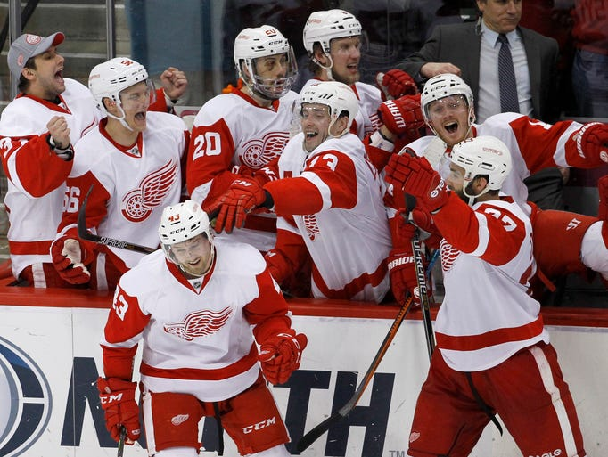 Detroit Red Wings players celebrate with center Darren