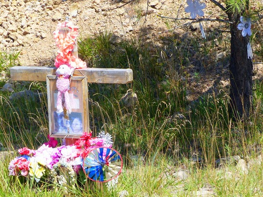 A memorial near the turnoff to a residential area on the Mescalero Apache Reservation displays photographs and includes artificial flowers hanging from a tree behind the cross.