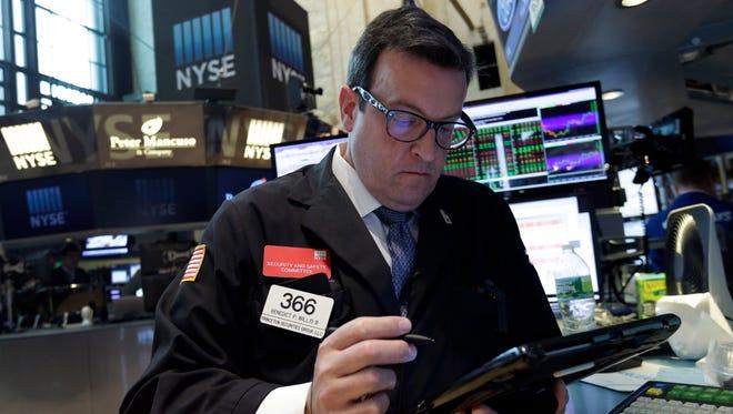 Trader Bebedict Willis works on the floor of the New York Stock Exchange, Wednesday, Aug. 12, 2015.