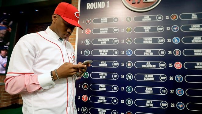 FILE - In this June 12, 2017, file photo, Hunter Greene, a pitcher and shortstop from Notre Dame High School in Sherman Oaks, Calif., stands near the draft board after being selected No. 2 by the Cincinnati Reds in the first round of the Major League Baseball draft in Secaucus, N.J. Greene has agreed to a minor league contract with a $7.23 million signing bonus–the highest since constraints on draft spending began in 2012. (AP Photo/Julio Cortez, File)