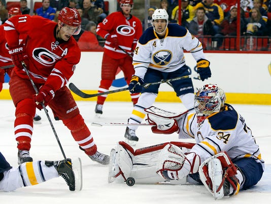 Carolina Hurricanes' Jordan Staal (11) charges into Buffalo Sabres goalie Michal Neuvirth (34), of the Czech Republic, during the second period of an NHL hockey game in Raleigh, N.C., Thursday, March 13, 2014. (AP Photo/Karl B DeBlaker)