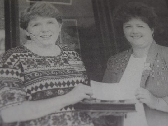 Lisa Hunt, left, of the Wal-Mart support management team, presented Morganfield Elementary School principal Betty Fox with a check for $250 for teacher appreciation week in August 1995.