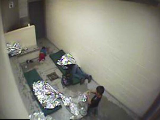 A woman and children are wrapped in Mylar sheets on