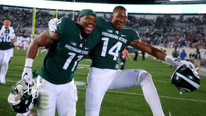 Michigan State's Jamal Lyles, left, and Kenney Lyke celebrate following a 28-13 win over Furman on Sept. 2, 2016, in East Lansing.