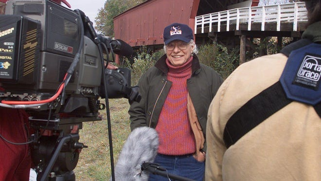 """In this 2002 file photo, author Robert James Waller tapes a Travel Channel segment on visits to places that have connections to movies. Waller recently donated a manuscript of his best-known novel, """"The Bridges of Madison County,"""" to the University of Northern Iowa's Rod Library."""