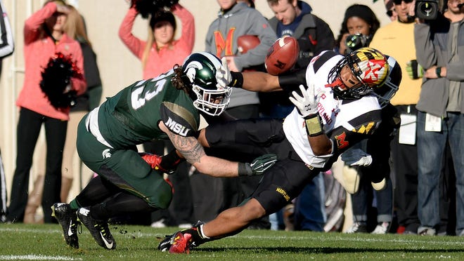 Linebacker Chris Frey (23) and another Spartan defender break up a catch by a Maryland receiver during the fourth quarter of the Spartans 24-7 victory, Saturday, November 14, 2015 at Spartan Stadium in East Lansing.